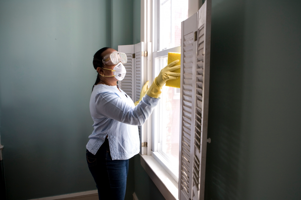 Lady disinfecting & cleaning her windows