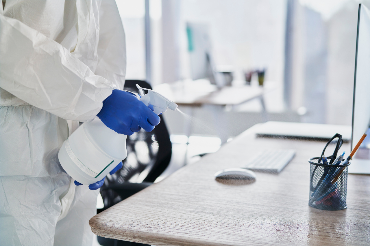 Cleaner sanitising workplace desks to protect office employees from COVID-19 pandemic