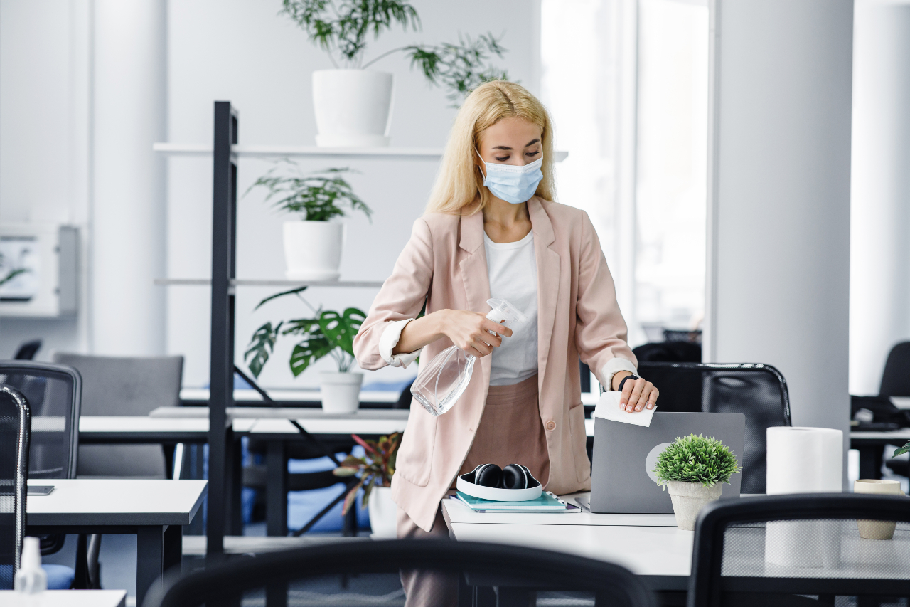 Employee wiping her desk with cleaning equipment to stay safe from COVID-19 virus