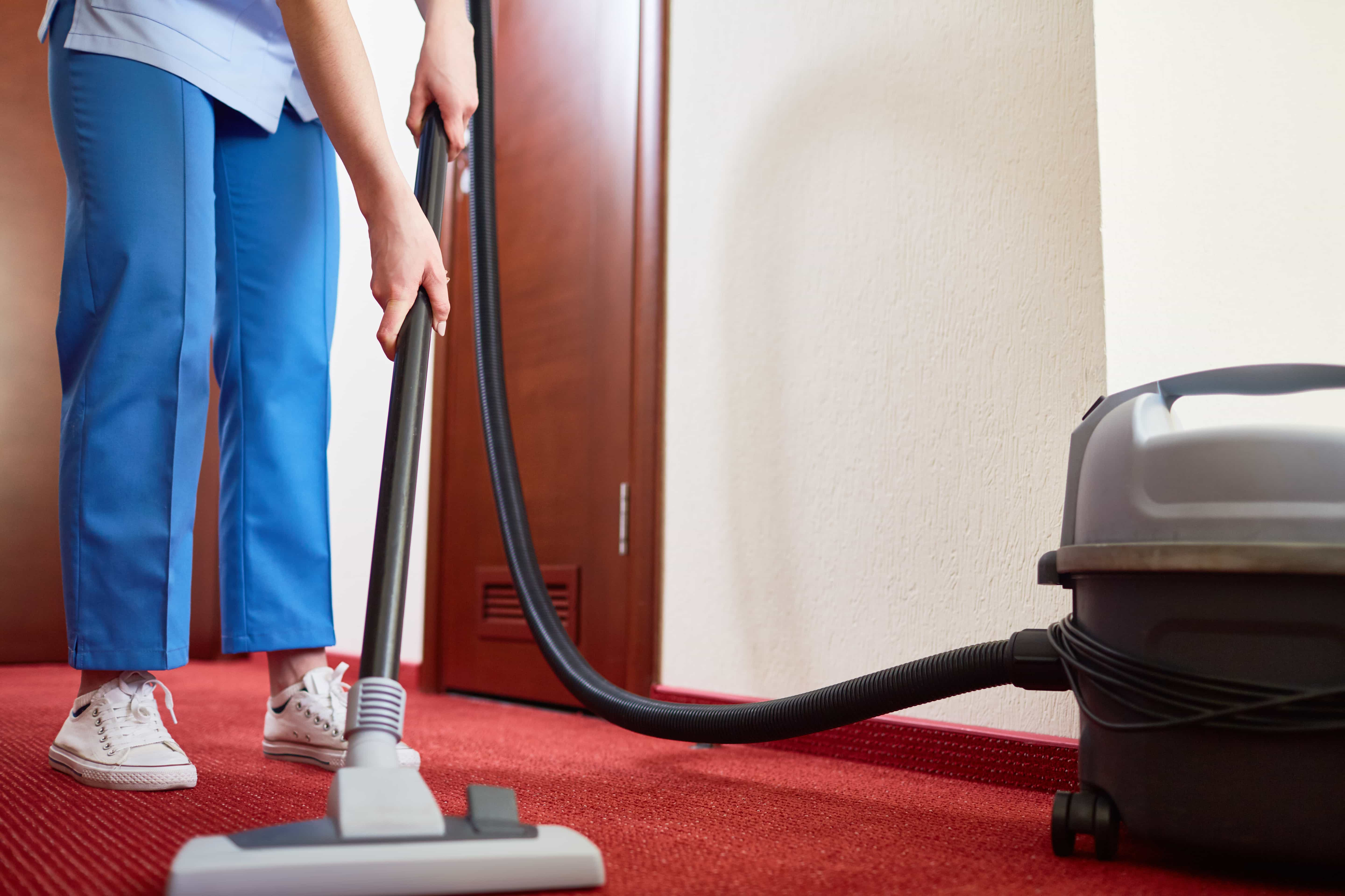 Commercial cleaner vacuuming carper in hotel room